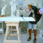 a stonecutter chiseling the pediment of a fireplace Frilli Gallery Marble Studio